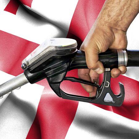 Gasoline consumption concept - Hand holding hose against flag of Georgia Foto de archivo