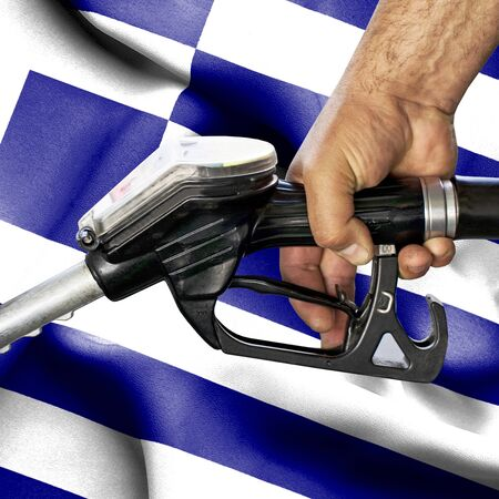 Gasoline consumption concept - Hand holding hose against flag of Greece