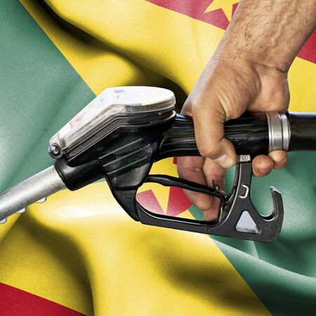 Gasoline consumption concept - Hand holding hose against flag of Guernsey Stok Fotoğraf