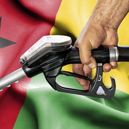 Gasoline consumption concept - Hand holding hose against flag of Guinea Bissau