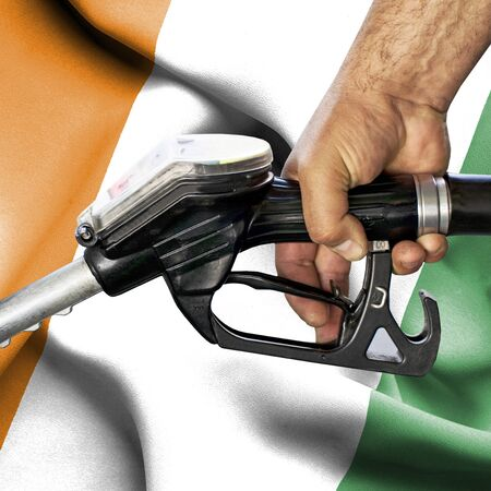 Gasoline consumption concept - Hand holding hose against flag of Ivory Coast