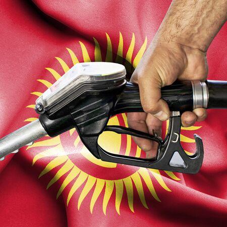 Gasoline consumption concept - Hand holding hose against flag of Kyrgyzstan