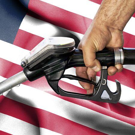 Gasoline consumption concept - Hand holding hose against flag of Liberia Foto de archivo