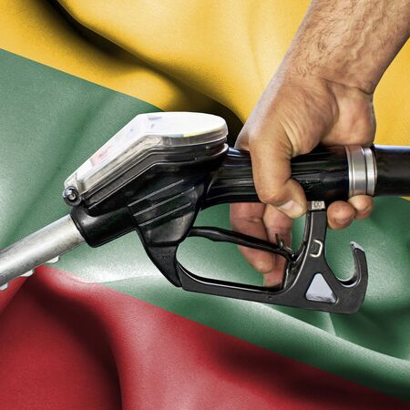 Gasoline consumption concept - Hand holding hose against flag of Lithuania