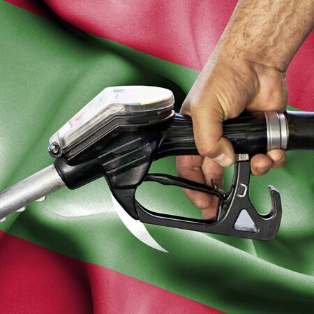 Gasoline consumption concept - Hand holding hose against flag of Maldives