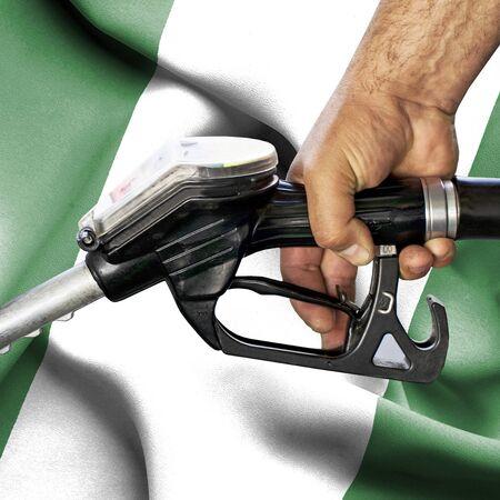 Gasoline consumption concept - Hand holding hose against flag of Nigeria