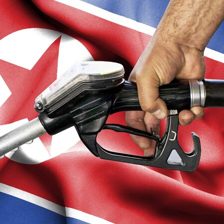 Gasoline consumption concept - Hand holding hose against flag of North Korea