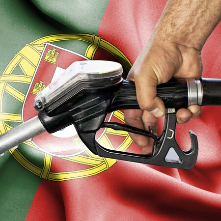 Gasoline consumption concept - Hand holding hose against flag of Portugal