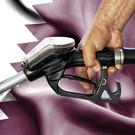 Gasoline consumption concept - Hand holding hose against flag of Qatar