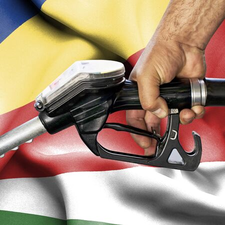 Gasoline consumption concept - Hand holding hose against flag of Seychelles
