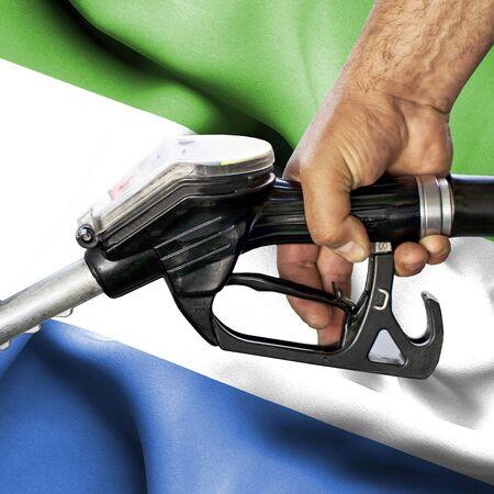 Gasoline consumption concept - Hand holding hose against flag of Sierra Leone