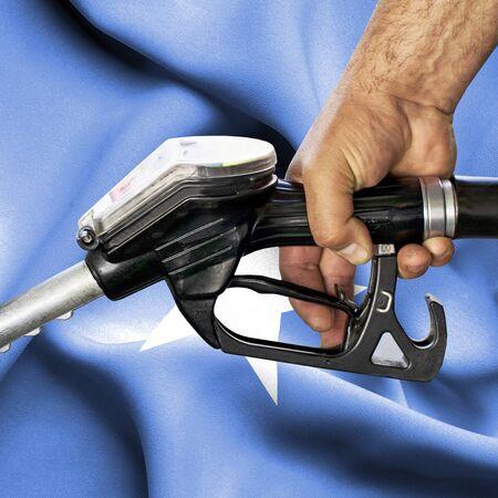 Consumo di benzina concetto - mano che tiene il tubo flessibile contro la bandiera della Somalia Archivio Fotografico