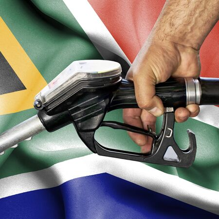 Gasoline consumption concept - Hand holding hose against flag of South Africa