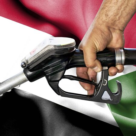 Gasoline consumption concept - Hand holding hose against flag of Sudan