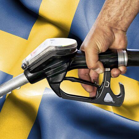 Gasoline consumption concept - Hand holding hose against flag of Sweden