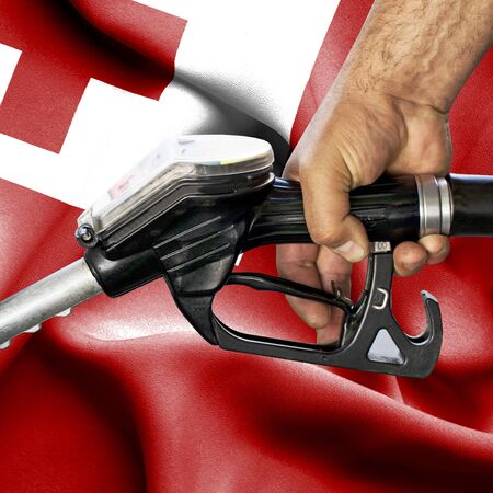 Gasoline consumption concept - Hand holding hose against flag of Tonga