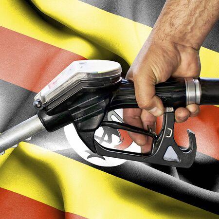 Gasoline consumption concept - Hand holding hose against flag of Uganda