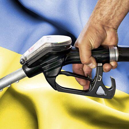 Gasoline consumption concept - Hand holding hose against flag of Ukraine