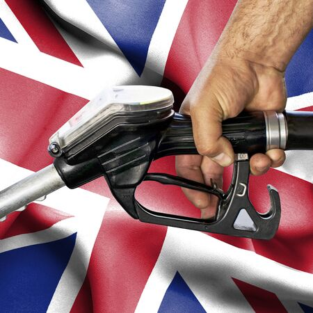 Gasoline consumption concept - Hand holding hose against flag of United Kingdom