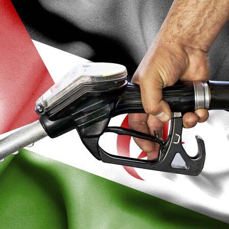 Gasoline consumption concept - Hand holding hose against flag of Western Sahara