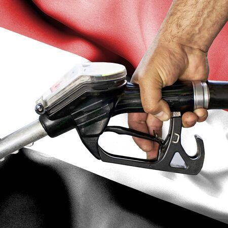 Gasoline consumption concept - Hand holding hose against flag of Yemen