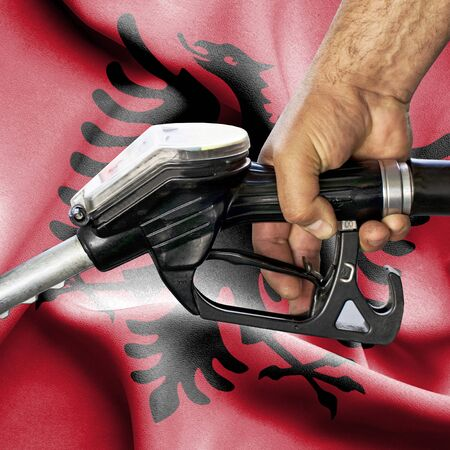 Gasoline consumption concept - Hand holding hose against flag of Albania