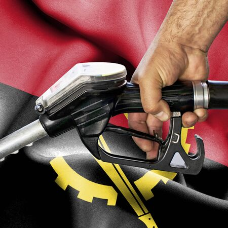 Gasoline consumption concept - Hand holding hose against flag of Angola