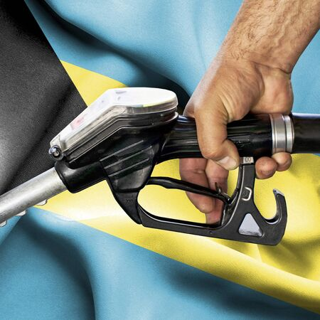 Gasoline consumption concept - Hand holding hose against flag of Bahamas Stok Fotoğraf