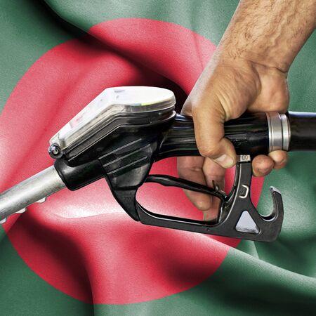Gasoline consumption concept - Hand holding hose against flag of Bangladesh