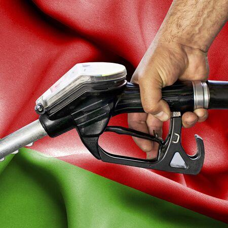 Gasoline consumption concept - Hand holding hose against flag of Belarus