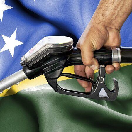 Gasoline consumption concept - Hand holding hose against flag of Solomon Islands