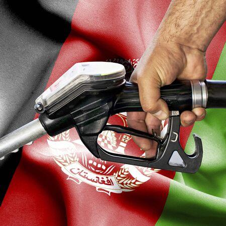 Gasoline consumption concept - Hand holding hose against flag of Afghanistan