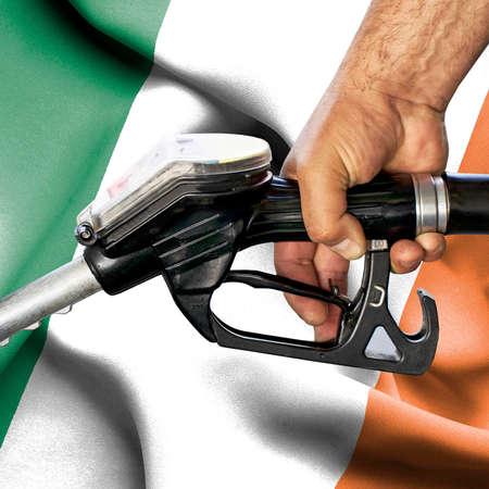 Gasoline consumption concept - Hand holding hose against flag of Ireland