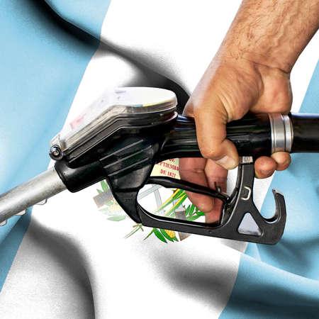 Gasoline consumption concept - Hand holding hose against flag of Guatemala