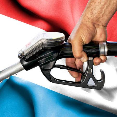 Gasoline consumption concept - Hand holding hose against flag of Luxembourg Foto de archivo