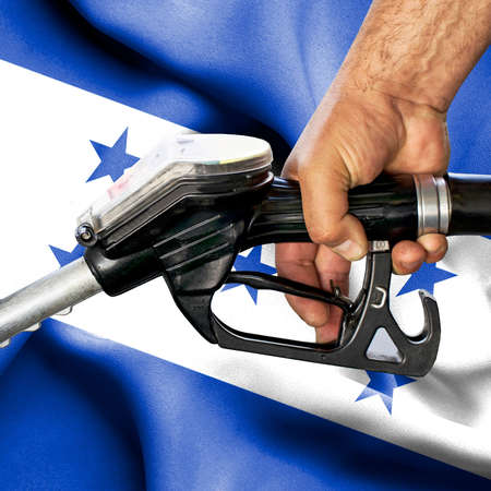Gasoline consumption concept - Hand holding hose against flag of Honduras