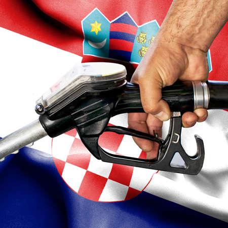 Gasoline consumption concept - Hand holding hose against flag of Croatia Archivio Fotografico