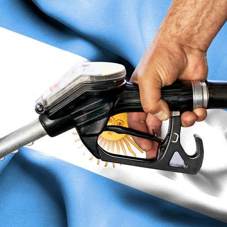 Gasoline consumption concept - Hand holding hose against flag of Argentina