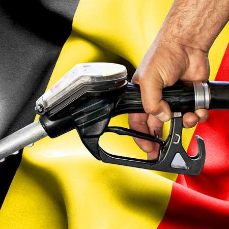 Gasoline consumption concept - Hand holding hose against flag of Belgium