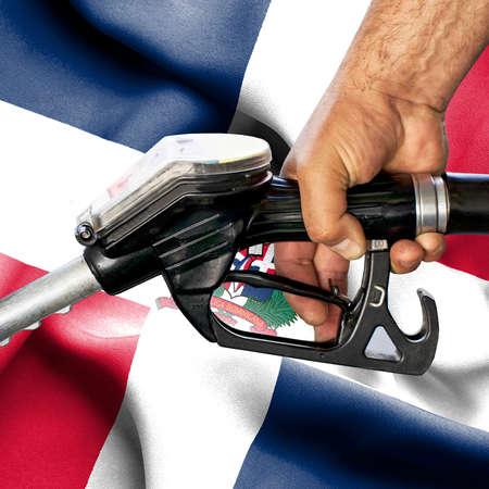 Gasoline consumption concept - Hand holding hose against flag of Dominican Republic Archivio Fotografico