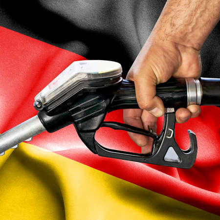 Gasoline consumption concept - Hand holding hose against flag of Germany