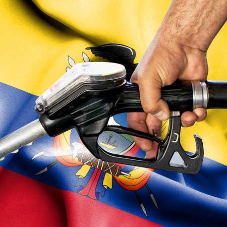 Gasoline consumption concept - Hand holding hose against flag of Ecuador