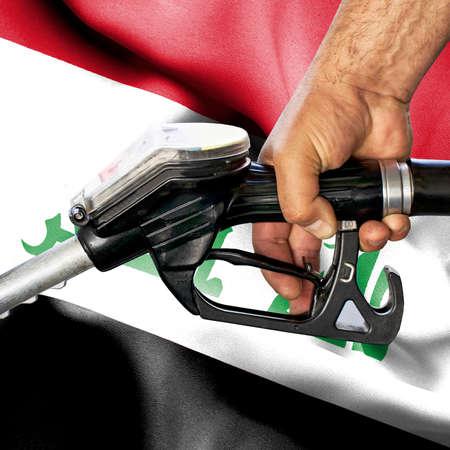 Gasoline consumption concept - Hand holding hose against flag of Iraq