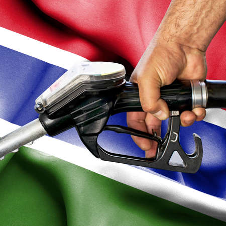 Gasoline consumption concept - Hand holding hose against flag of Gambia