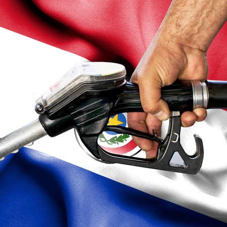 Gasoline consumption concept - Hand holding hose against flag of Paraguay