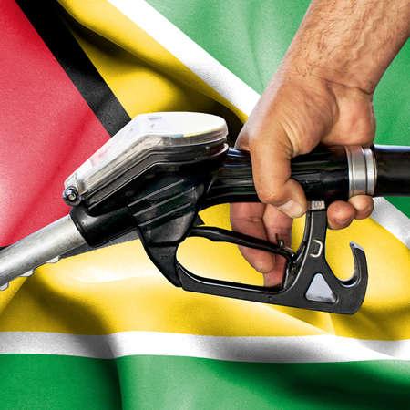 Gasoline consumption concept - Hand holding hose against flag of Guyana Foto de archivo