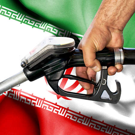 Gasoline consumption concept - Hand holding hose against flag of Iran
