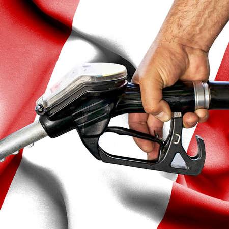 Gasoline consumption concept - Hand holding hose against flag of Peru