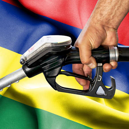 Gasoline consumption concept - Hand holding hose against flag of Mauritius