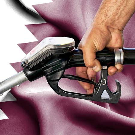 Gasoline consumption concept - Hand holding hose against flag of Qatar